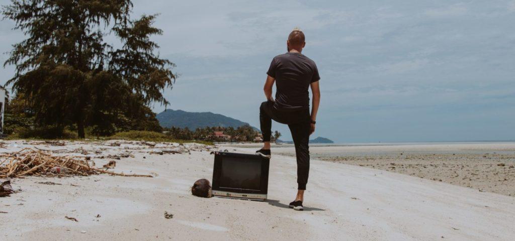 man with TV on a beach